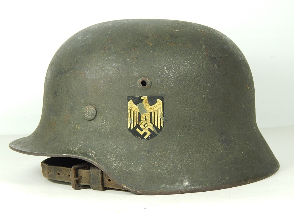 An early production M35 Heer helmet with a matte field gray over-paint. The paint applied per the March 1940 regulations, the national colors decal was painted over in this case Note the  M27 Reichwehr era chinstrap