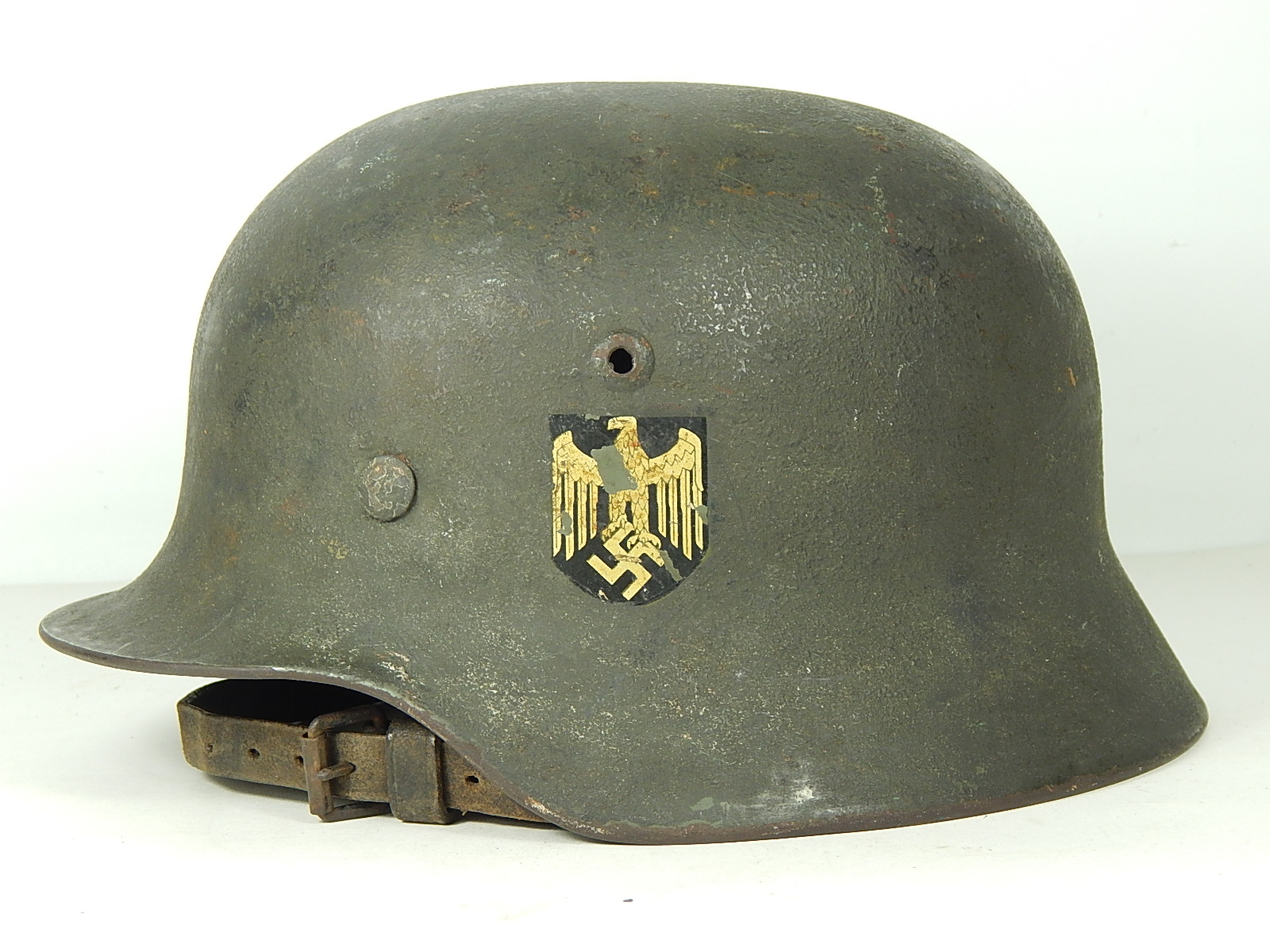 An early production m35 heer helmet with a matte field gray over paint the
