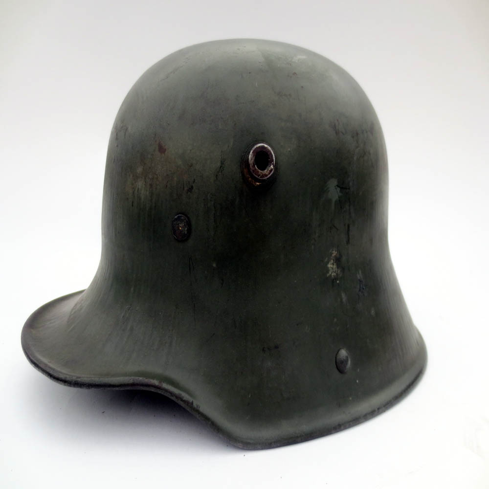 This lightly worn M16 is an excellent example of a helmet issued with a matte finish. The matte paint was an early attempt to create a finish which more easily blended in with the surrounding landscape. This helmet was a direct vet purchase in the 1960s. The helmet's finish exhibits mostly storage wear, and appears almost as it might have in 1917 when it was issued.