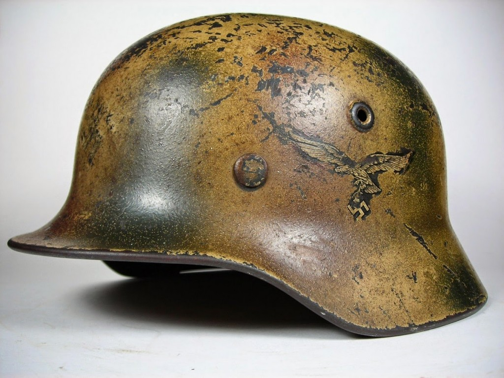 "Luftwaffe M40. The helmet has been sprayed with a 3-color camouflage pattern sometimes called ""Normandy camo"" The Luftwaffe decal was carefully masked off prior to the paint application."