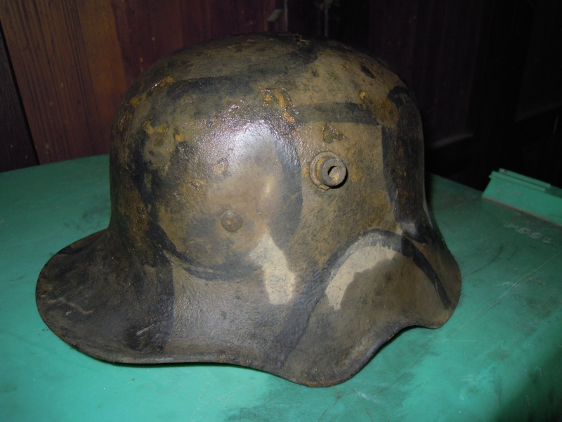 This camouflaged M18 cut-out represent one of less that 100,000 that were made. Lack of photographic evidence has led some to believe this model saw little combat use. This discovery of this helmet in the cache verifies that many did in fact see action