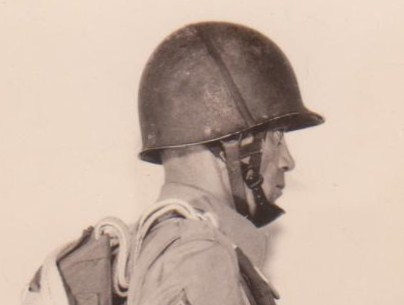 Army training photo of a paratrooper wearing a M2. He as secured he liner chinstrap over the dome of his helmet, probably to further secure the liner to the helmet