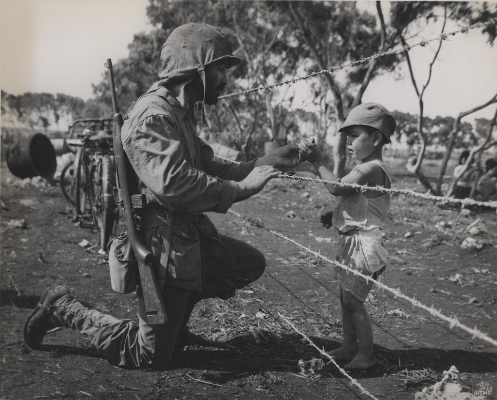 Marine chats with a Japanese civilian boy. He wears the flaps of his helmet cover out protecting his neck from the Pacific sun.