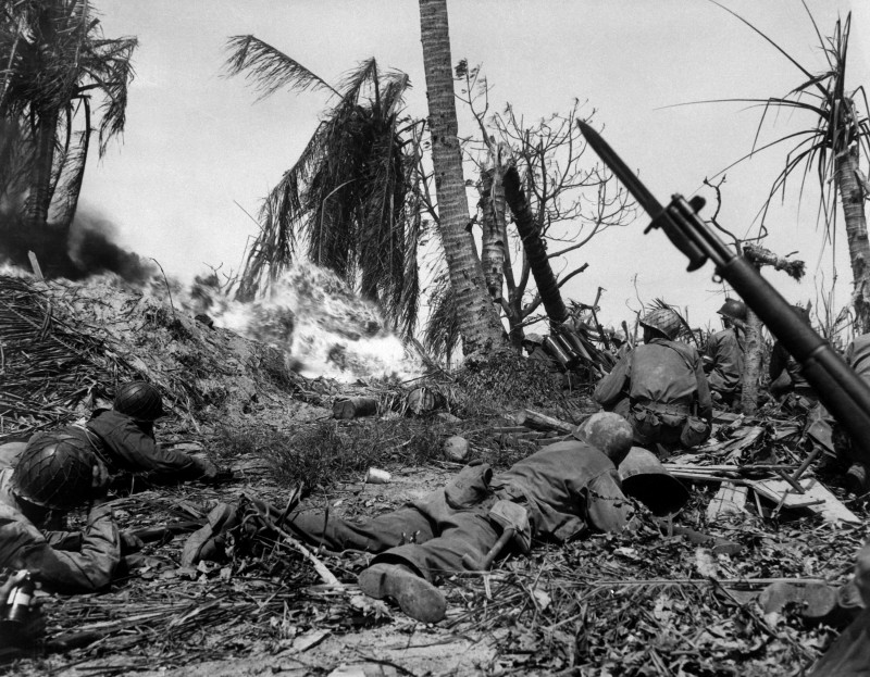 Men of the 7th Div. using flame throwers to smoke out Japs from a block house on Kwajalein Island, while others wait with rifles ready in case Japs come out. February 4, 1944. Cordray. (Army) NARA FILE #: iii-SC-212770 WAR & CONFLICT BOOK #: 1187