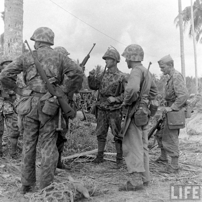 Marines on Bougainville. These men wear covers without the button holes. One man has added a net over his cover for foliage since he does not have button holes in his cover