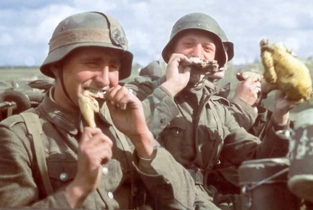 color German soldiers celebrating joyful eating roast chicken
