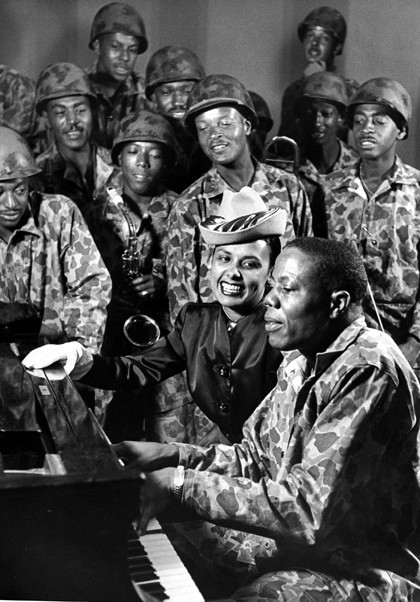Singer Lena Horne singing next to pianist Silky Hendricks of the 299th Ground Force Band, aka the Jungleers. These men all wear Westinghouse jungle liners.