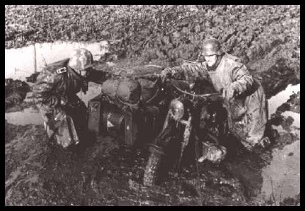 Stuck in the mud at Stalingrad. The man to the right wears a Hungarian camouflage helmet cover.