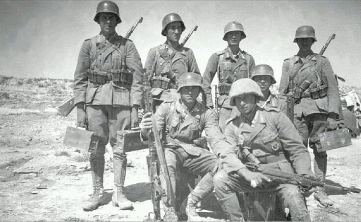 A squad of German soldiers. One wears a hessian cloth cover