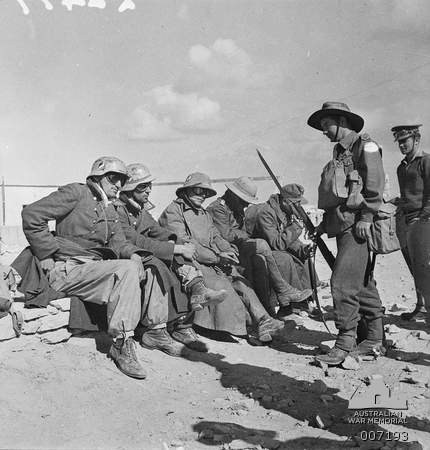 Australian soldiers watch over captured members of the DAK. Note that two of the German wear M35 with national colors decal which were camoflaged around