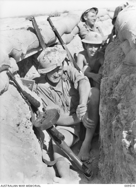 Australian troops at Tobruk, both men wear helmets camoflaged with tan paint