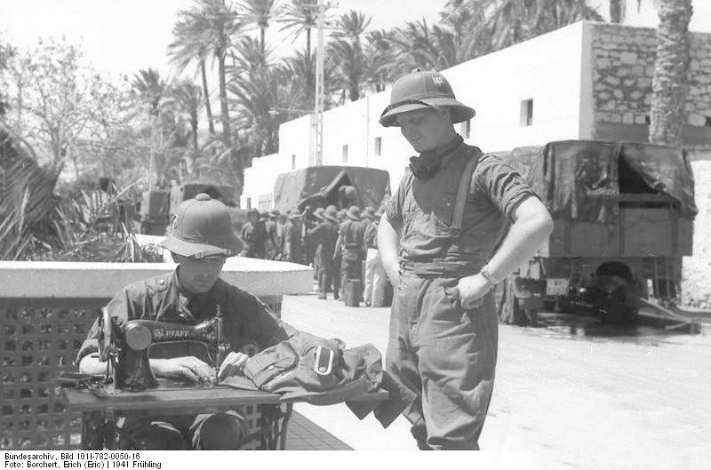 Tripoli 1941. A German soldier waits while his companion makes repairs on his tunic. Both wear the so called M1940 Pith Helmet