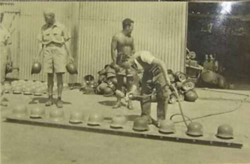German helmets in a North African supply depot being repainted tan for service in the desert