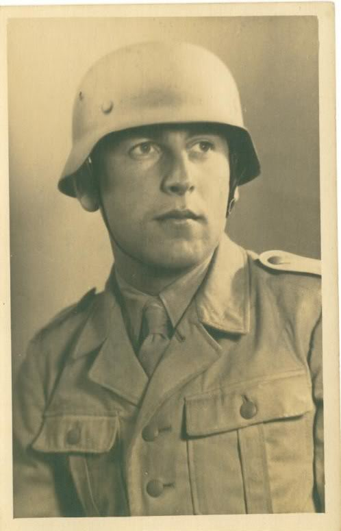 Studio photo of a German soldier wearing a M35 helmet. HIs helmet was sprayed tan directly over the smooth factory paint